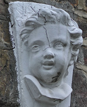 A white cherub's face above one of the house doorways.