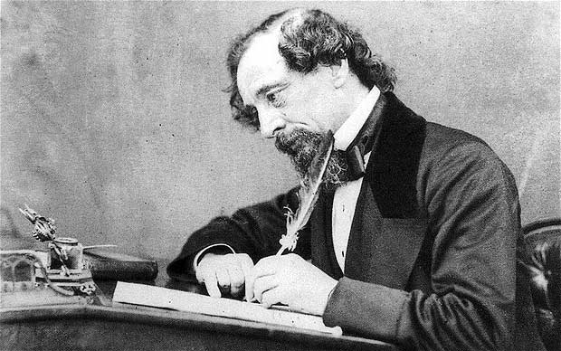 Charles Dickens writing at his desk.