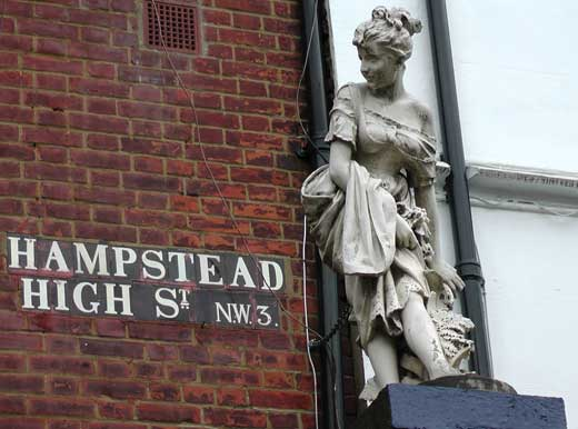 The Hampstead High Street sign with a statue of a lady to its right.